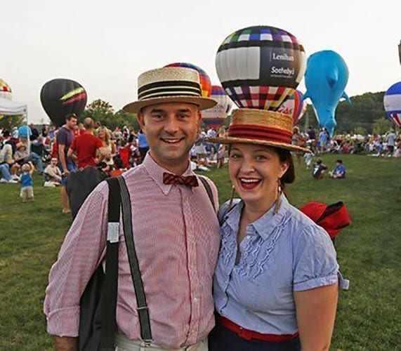 A couple poses in front of hot air balloons