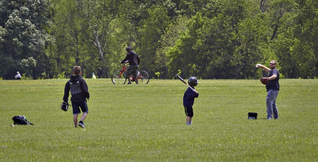 A family play baseball in Broad Run Park
