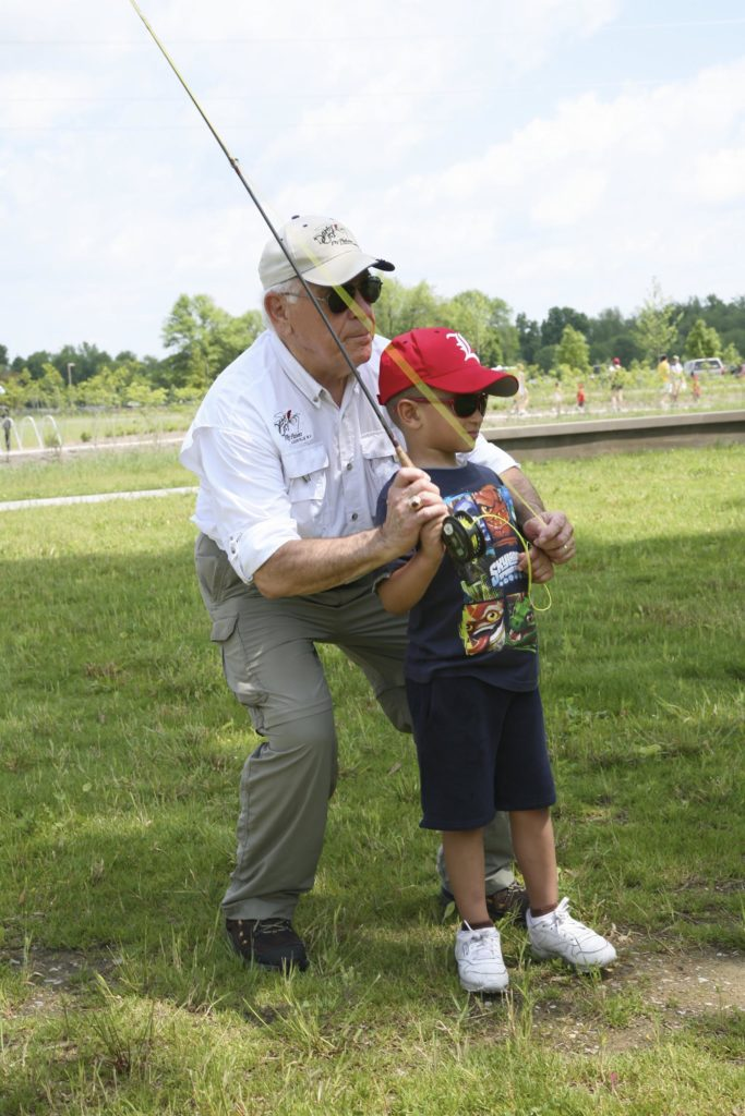 An elderly man and little boy fish together