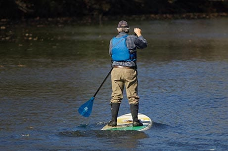 A man paddles on a river