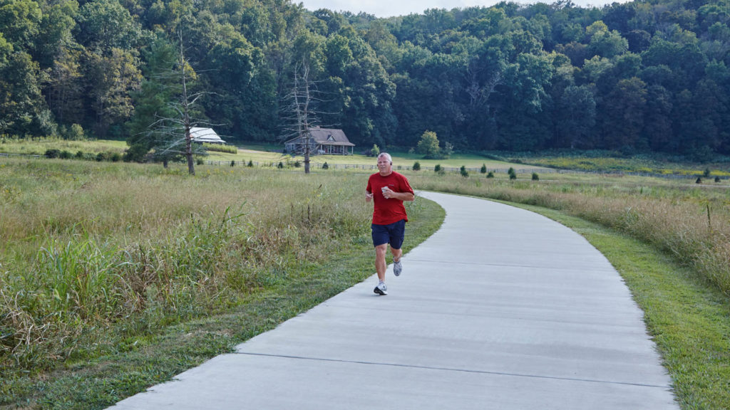 Man jogs on a walking path