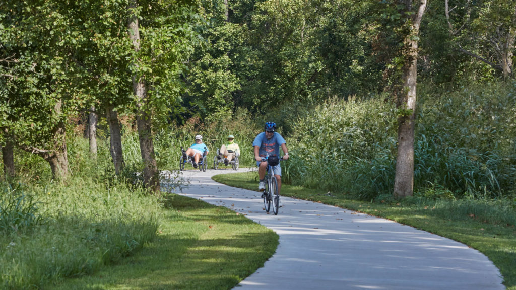 Bicyclists ride on a walking path