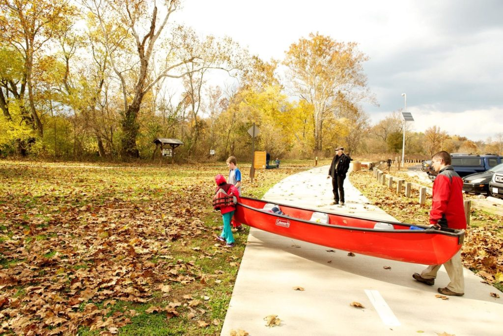 A family walks a canoe to a river